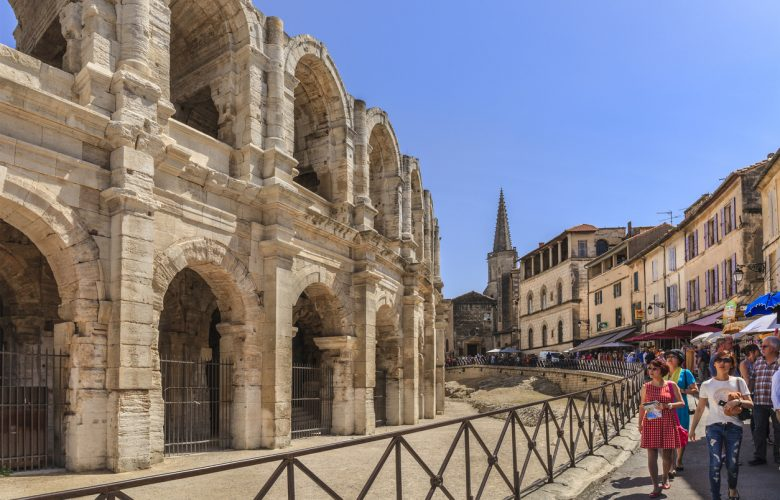 Arles, France - June 6, 2014: Tourists strolling in the old town of Arles, next to the Roman Amphitheatre, one of the main sights of the city. Built in about 80 AD, the amphitheatre was capable of seating over 20,000 spectators, which attended the bloody hand-to-hand combats typical of that period.